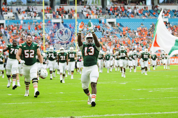 """DeeJay Dallas throws up the """"U"""" as the team runs onto the field"""
