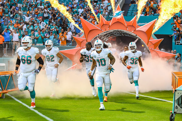 Miami Dolphins run through the smoke and fire