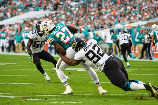 Jacksonville Jaguars defensive end Lyndon Johnson (92) tackles Miami Dolphins running back Kalen Ballage (27) for a loss