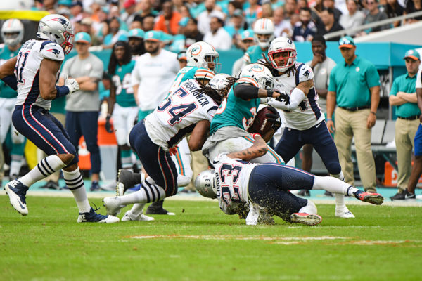 New England Patriots strong safety Patrick Chung (23) and New England Patriots outside linebacker Dont'a Hightower (54) tackle Miami Dolphins running back Kenyan Drake (32)