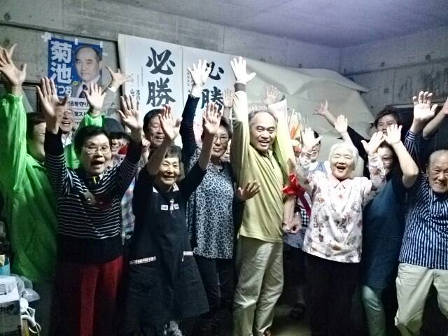 集まった支持者らと当選を喜ぶ菊池むつお氏(中央)