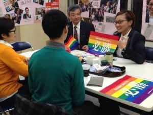 池内候補(右奥)に、当選を祈願する虹色の旗を贈る 後援会メンバー(手前)。左奥は、そねはじめ都議 =7日、東京都内