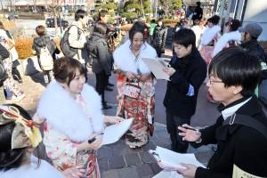 成人式会場前で新成人と対話する民青同盟員=12日、渋谷区