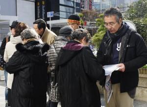 参加者の呼びかけに応じて続々と署名する女性ら=16日、東京・新宿駅前