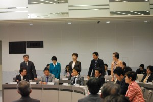 共産党提案の予算組み替え案に賛成して起立する党都議団=25日、東京都議会