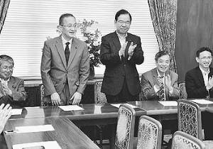 復帰のあいさつを述べる笠井亮衆院議員(左から2人目)と、拍手をおくる志位和夫委員長(その右)、同僚議員たち=16日、国会内