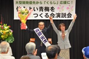 演説会で声援にこたえる斉藤光次市長候補(左)と田村智子参院議員(右)=3日、東京都青梅市