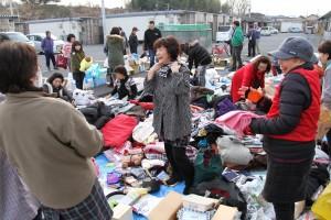 「無料バザー」で衣類をさがす人たち=23日、宮城県石巻