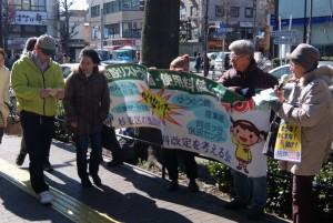 宣伝する人たち(右側)と、ビラを受け取り目を通す通行人(左側)=10日、東京都杉並区・杉並区役所通り(「しんぶん赤旗」提供)