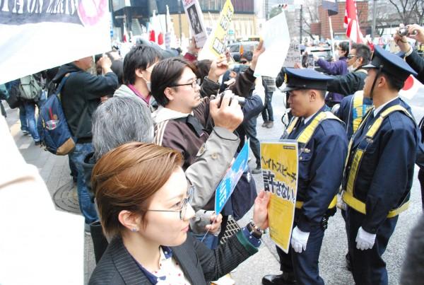 ヘイトデモ(右奥、警官隊の後方)に向けて差別反対のスローガンが印刷されたカードを掲げる池内さおり衆院議員(左手前)らカウンター行動の参加者=6日、東京・銀座