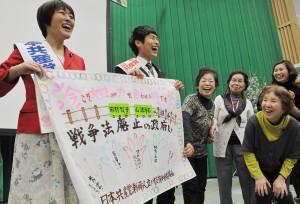 送られたプレゼントを手に笑顔の田村智子参院議員(左)と山添拓参院東京選挙区候補=5日、党本部