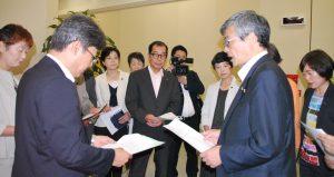 担当者(左手前)に申し入れる曽根はじめ副団長(右手前)と党都議団=17日、東京都庁(「しんぶん赤旗」提供)