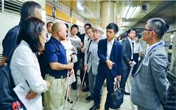 (写真)東視協の山城さん(左から3人目)に質問する党議員団=25日、東京都港区