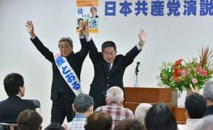 声援に手を上げてこたえる小池書記局長(右)と綾都議候補=28日、東京都大島町