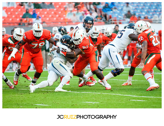 Hurricanes lineman, #90 Ufomba Kamalu, wraps up Virginia RB, #25 Kevin Parks