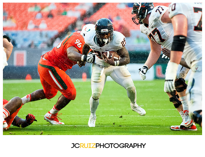 Virginia RB, #25 Kevin Parks, tries to elude the tackle of Hurricanes #96, Curtis Porter
