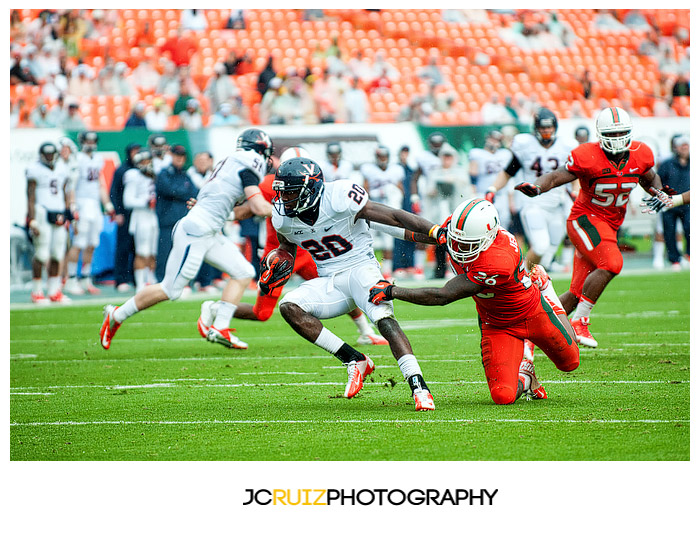 Virginia RB #20, Tim Smith, eludes the tackle of Hurricanes #26, Rayshawn Jenkins