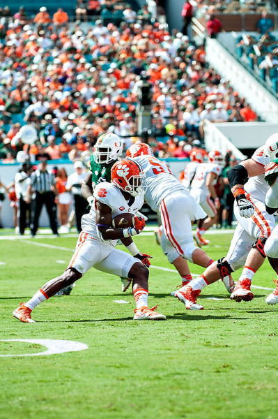 Clemson Tigers RB #9, Wayne Gallman, attempts to rush past the Miami Hurricanes defense