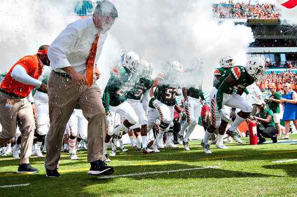 The Miami Hurricanes run through the smoke