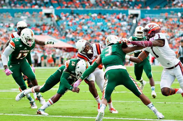 Miami Hurricanes safety #26, Rayshawn Jenkins, tries to stop Virginia Tech RB #34, Travon McMillian, from scoring