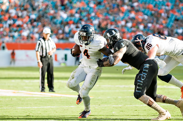 Taquan Mizzell tries to run past a Hurricanes defender