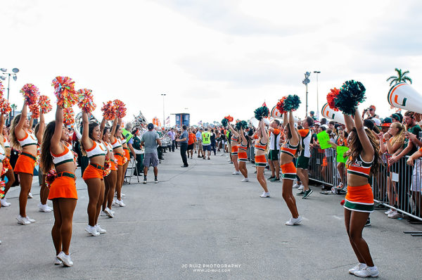 Hurricane cheerleaders and band wait for the team to arrive