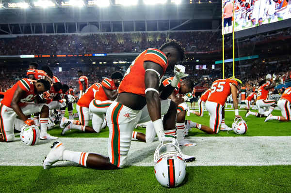 Hurricanes TE, David Njoku, takes a knee in prayer before the game