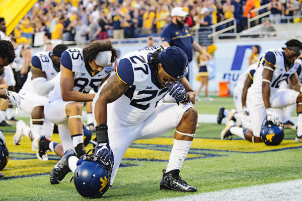 Sean Walters, West Virginia LB, takes a knee in prayer before the game