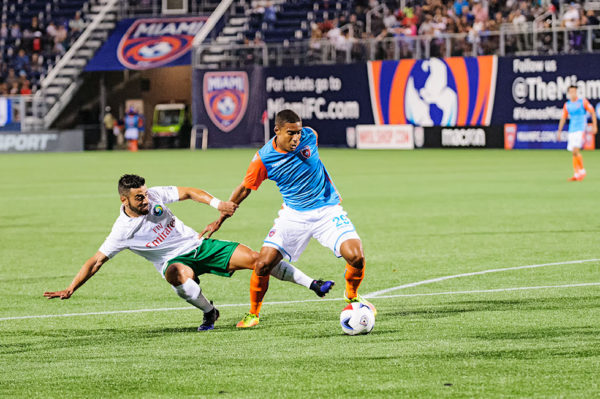Miami FC forward, Stefano Pinho, tries to keep the ball away from the defender
