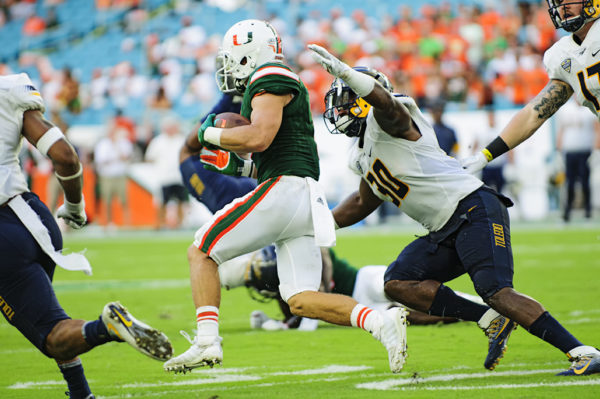 Hurricanes WR, Braxton Berrios, tries to run past defenders