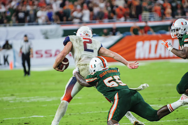 Shaquille Quarterman (55) wraps up Eric Dungey (2)
