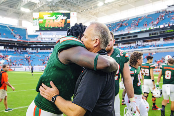 Chad Thomas and Mark Richt embrace after the game