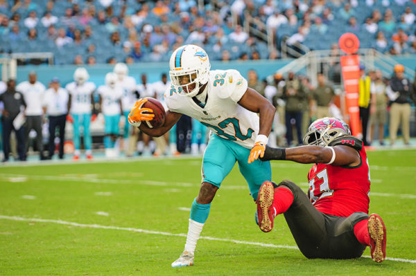 Kenyan Drake (32) tries to escape the clutches of Gerald McCoy (93)