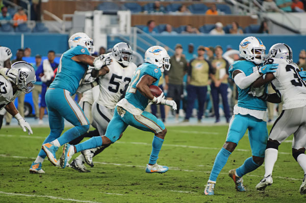 Kenyan Drake (32) runs through a hole