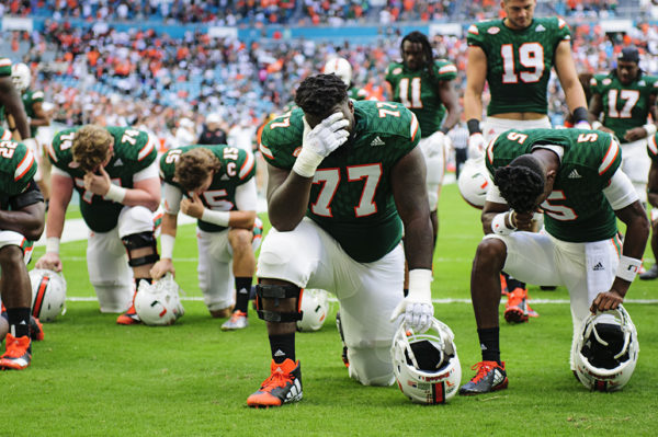 Players take a knee for prayer before the game