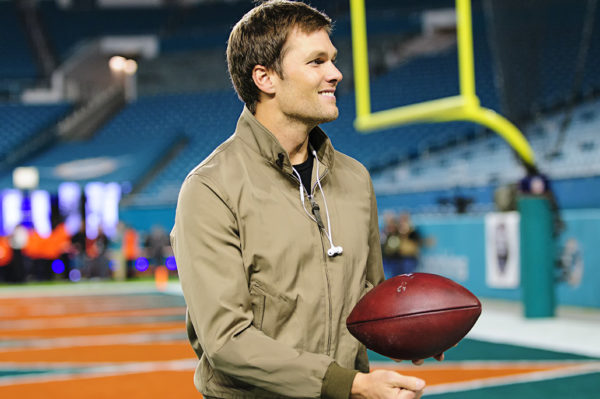 Tom Brady walks to the locker room after chatting with former coach Charlie Weis on the field prior to the game against the Dolphins