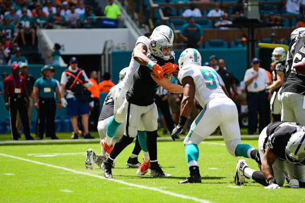 Miami Dolphins defensive end Robert Quinn (94) hits Oakland Raiders quarterback Derek Carr (4) as he throws