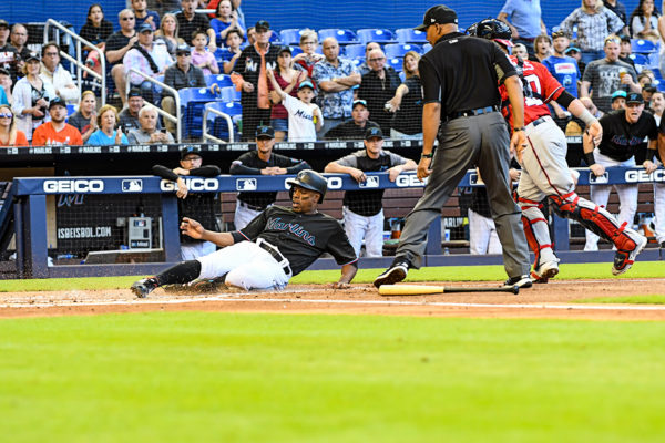 Miami Marlins left fielder Curtis Granderson #21 slides across home plate