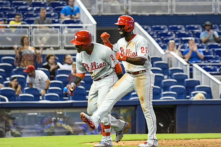 Philadelphia Phillies center fielder Andrew McCutchen (22) is all smiles after greeting Philadelphia Phillies shortstop Jean Segura (2)