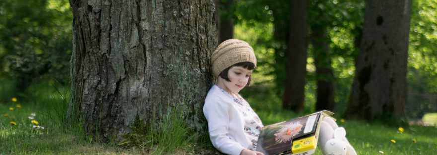 Little girl reading a book under big linden tree