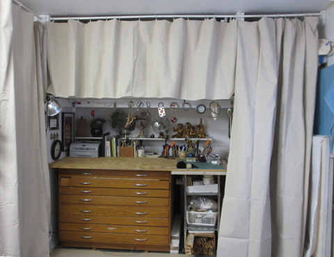 Curtains hiding storage racks.