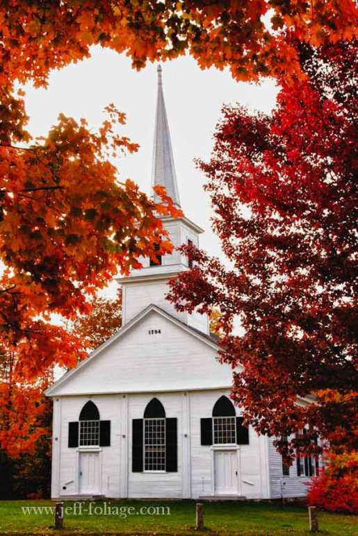 New England fall foliage in New Salem Massachusetts. White church with late afternoon sun in the fall leaves.