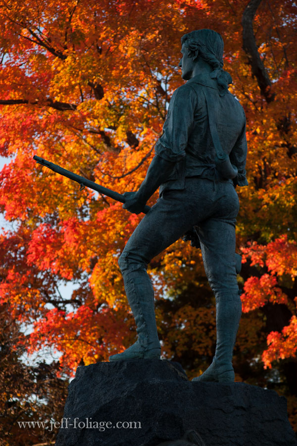 Lexington Minuteman Park in Lexington Massachusetts, with fall colors behind the Minuteman statue