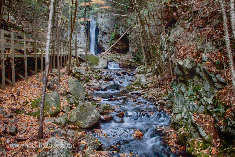 on the property of the castle in the clouds the state line many streams such as this one which has a small waterfall and a wooden walkway to get up close to the waterfall