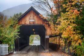 Middle bridge in Woodstock Vermont is a covered bridge with fall foliage around the entrance