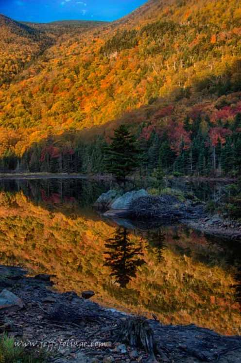 the morning sun rise above the hills above the beaver pond which is north of Woodstock New Hampshire. The sun lit up the peak fall foliage on the walls of the bowl.