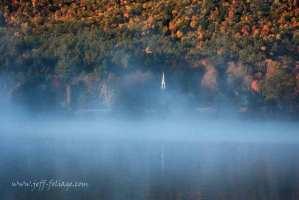 New Hampshire fall foliage rises above a little white church in Eaton NH.
