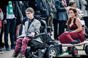 Boy driving electric wheelchair pulling cart with prom date on the back