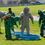 Two men in hazmat suits spraying down a 3rd man in a hazmat suit standing in a kiddie pool