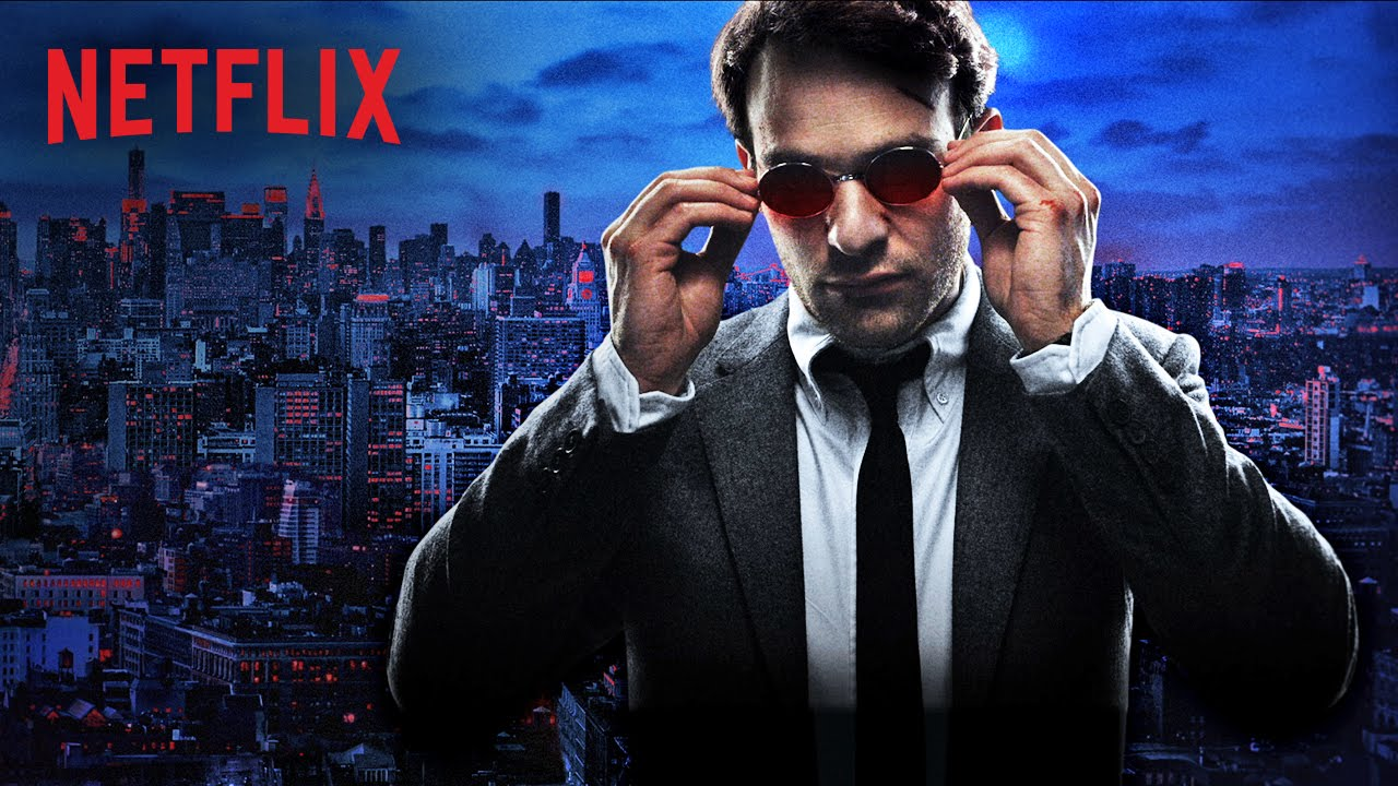Matt Murdock in a suit and sunglasses standing in front of a cityscape